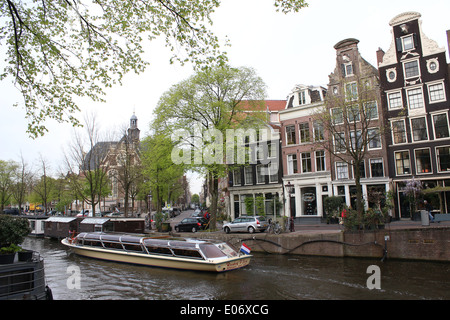 Canal boat  passing historic houses along Prinsengracht canal in Amsterdam, The Netherlands. Noorderkerk church - Stock Photo