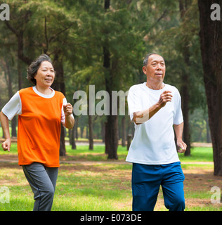 happy senior couple jogging together in the park - Stock Photo
