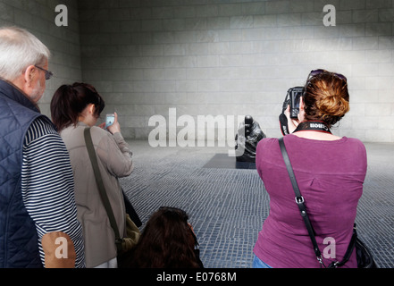 Tourists taking photographs of Kathe Kolwitz's sculpture 'Mother with her Dead Son' in Neue Wache, Berlin - Stock Photo