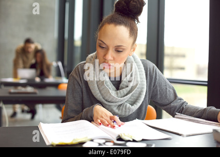 Female student reading a book for finding information. Young african american woman sitting at table doing assignments. - Stock Photo