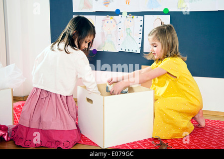 Two Girls Playing in Nursery - Stock Photo