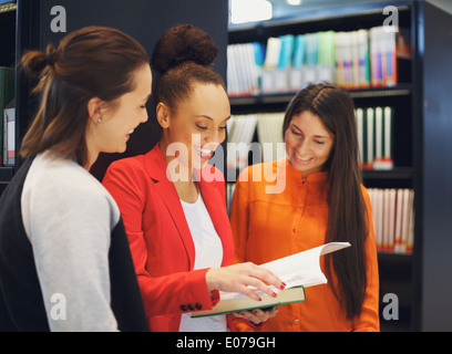 Diverse group of college students in library reading a book together. Female students looking for information in - Stock Photo