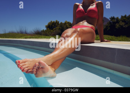 Low angle view of female model relaxing by the pool with her legs in water. Young woman in bikini sunbathing by - Stock Photo