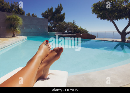Bare feet of young lady lying on deck chair sunbathing by the swimming pool. - Stock Photo