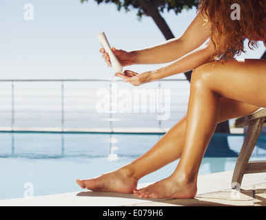 Woman sitting on deck chair by the swimming pool applying sun cream onto her legs. Female model sunbathing at the - Stock Photo
