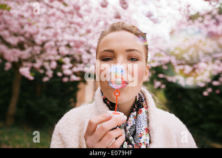 Portrait of beautiful young woman blowing bubbles at park. Pretty female model with bubble wand at spring blossom - Stock Photo
