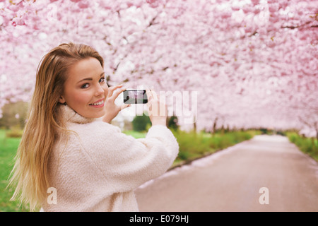 Young woman using her smartphone to capture images of the path and cherry blossoms tree at park, Young female looking - Stock Photo