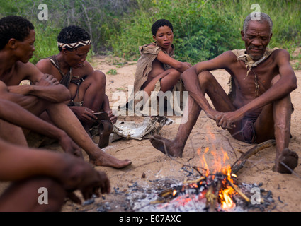Bushman People Around A Fire In A Traditional Village, Tsumkwe, Namibia - Stock Photo