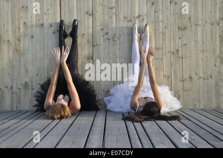Illustration - Two women wearing a black and a white tutu lie on a wooden floor with stretched arms and legs at - Stock Photo