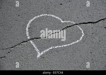 Illustration - A chalk heart is painted on a cracked asphalt road in Germany, 02 June 2011. Photo: Berliner Verlag/Steinach - Stock Photo
