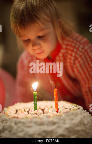 Little girl blowing out birthday candles on cake - Stock Photo