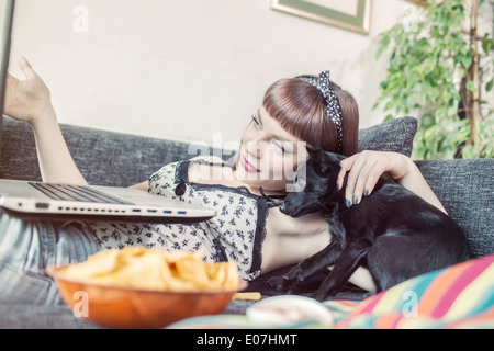 Young woman using laptop alongside her pet dog - Stock Photo