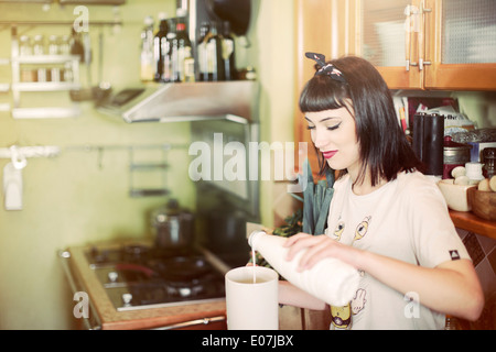Young woman preparing a milk drink in kitchen - Stock Photo