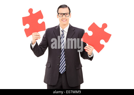 Young businessman holding two pieces of puzzle - Stock Photo