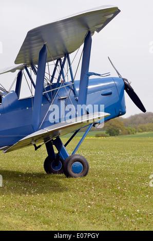 Blue  de Havilland DH.82 Tiger Moth biplane on a grass airstrip in Hampshire, England. - Stock Photo