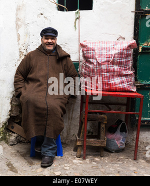 Man sitting on a chair and smiling in Tetouan Medina, Morocco - Stock Photo