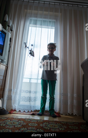 Boy 8 9 play toy helicopter playing home remote - Stock Photo