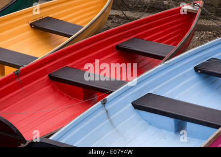 Various colored boats lined up on shore - Stock Photo
