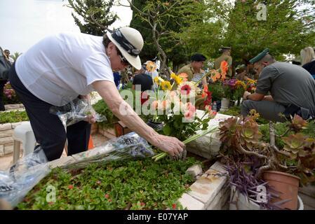 Tel Aviv, Israel. 5th May, 2014. TEL AVIV, ISRAEL - MAY 05: An Israeli elder woman places flowers on the grave of - Stock Photo