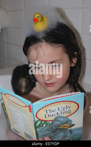 Young girl in the bath reading the ugly duckling story  to her real pet duckling who is sitting on her shoulder, - Stock Photo