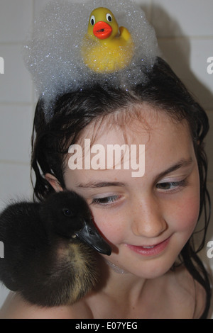 Girl and her real pet Cayuga duckling having a bath, duckling sitting on girls shoulder, bath time, UK - Stock Photo