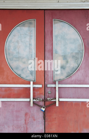 Padlocked door of an old abandoned movie theater. - Stock Photo