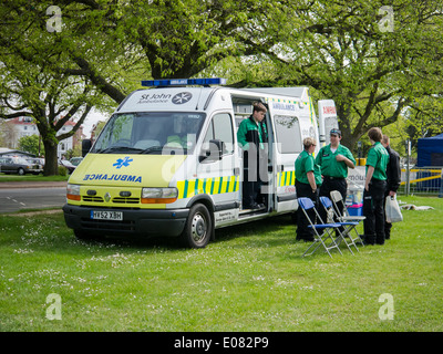 Members of St. John Ambulance providing emergency first aid cover from an ambulance at a community event. - Stock Photo