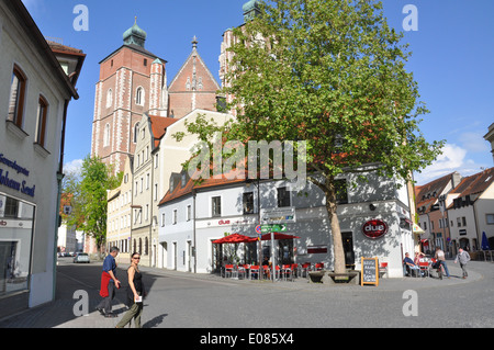 Two people crossing the street with the Ingolstadt Munster in the background. - Stock Photo