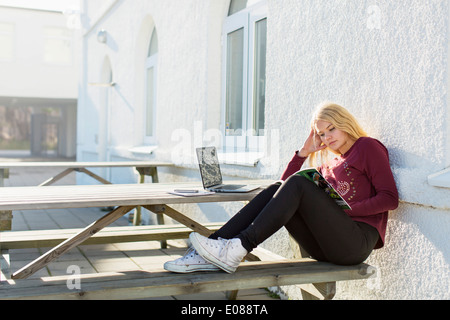 Full length of teenage girl reading book at picnic table - Stock Photo