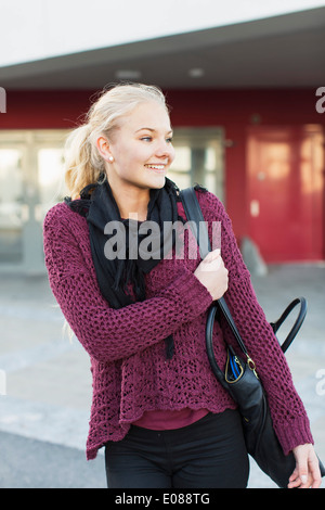 Happy teenage girl looking away on high school campus - Stock Photo