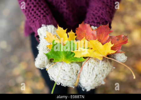 Midsection of teenage girl holding autumn leaves outdoors - Stock Photo