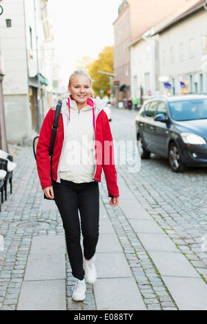 Full length of teenage girl walking on footpath - Stock Photo