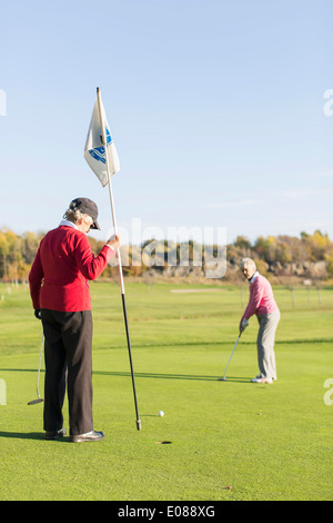Senior woman putting while friend holding flag on golf course - Stock Photo
