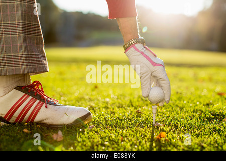 Cropped image of senior woman placing golf ball on tee - Stock Photo
