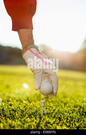 Woman placing golf ball on tee - Stock Photo