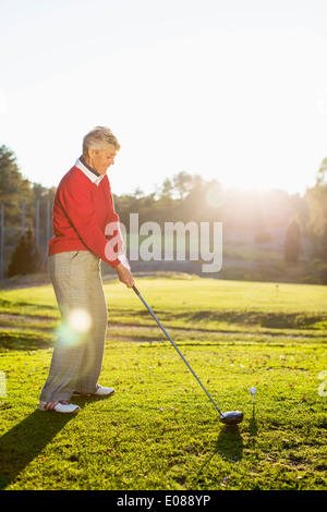 Full length side view of senior woman playing golf on course - Stock Photo