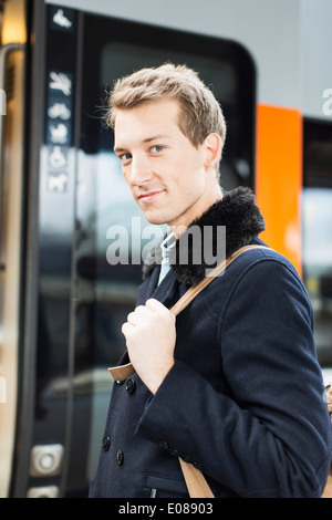 Portrait of confident young businessman at railroad station - Stock Photo