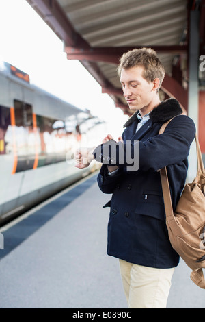 Young businessman looking at watch on railroad station - Stock Photo