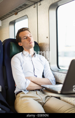 Thoughtful young businessman on train - Stock Photo