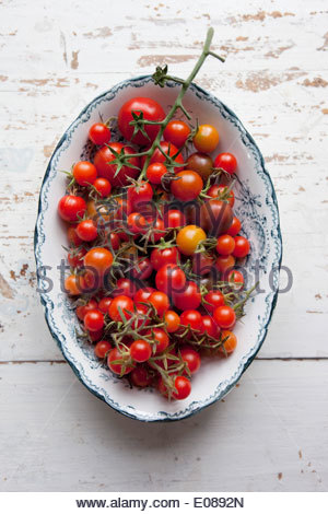 Directly above shot of cherry tomatoes in container on wood - Stock Photo
