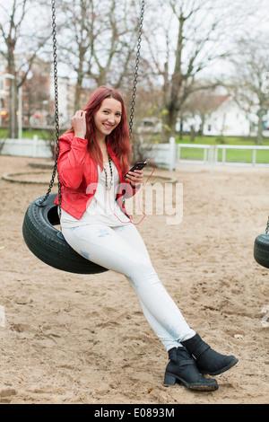 Full length of happy teenage girl enjoying music on tire swing in playground - Stock Photo