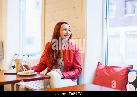 Happy teenage girl looking away at cafe - Stock Photo