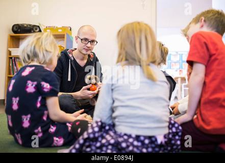 Teacher playing with children in kindergarten - Stock Photo