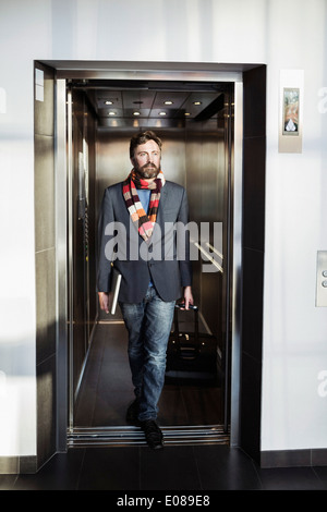 Businessman coming out from elevator in hotel - Stock Photo