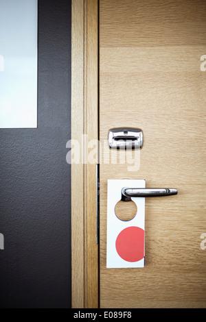 Label hanging on door handle in hotel - Stock Photo