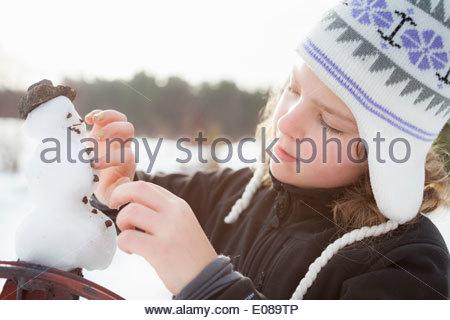 Little girl making snowman outdoors - Stock Photo