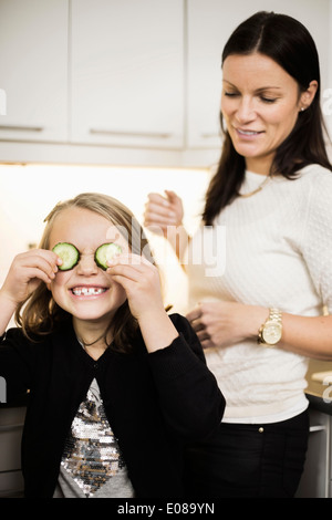 Mother looking at daughter covering eyes with cucumber slices - Stock Photo