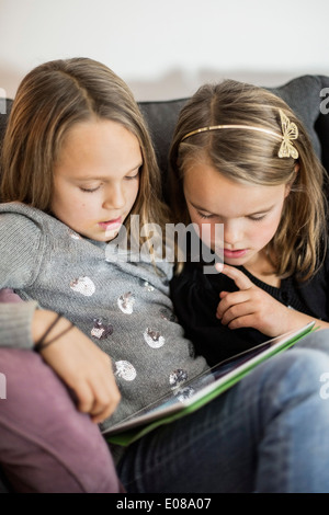 Siblings using digital tablet together on sofa - Stock Photo