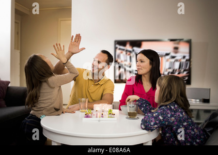 Father and daughter giving high-five while playing ludo at coffee table - Stock Photo