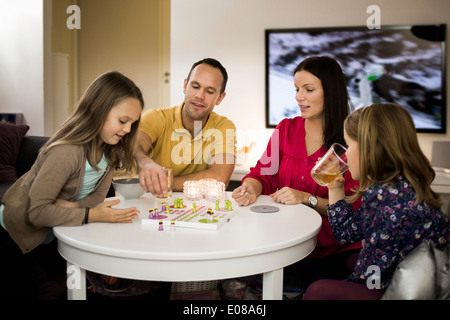 Family playing ludo in living room - Stock Photo
